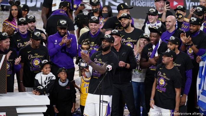 Los Angeles Lakers' LeBron James (23) holds the trophy as he celebrates with his teammates after the Lakers defeated the Miami Heat 106-93 in Game 6 of basketball's NBA Finals Sunday, Oct. 11, 2020, in Lake Buena Vista, Fla.