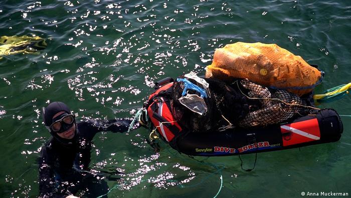 El organizador de Opération Mer Propre, Laurent Lombard, arrastrando mascarillas, guantes y otros residuos a la orilla después de recuperarlos del fondo del océano.