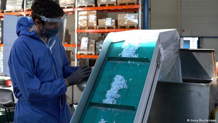 A Plaxtil worker surveys shreds of disposable mask during the UV light decontamination process.