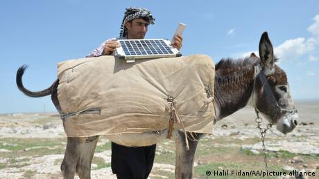 Shepherd charging his phone with solar panels on a donkey