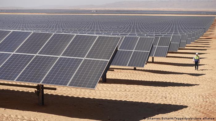 Solarpark Benban in der Wüste von Ägypten auf einer Fläche von 37 Quadratkilometer. Ein Mann geht neben der Anlage entlang.