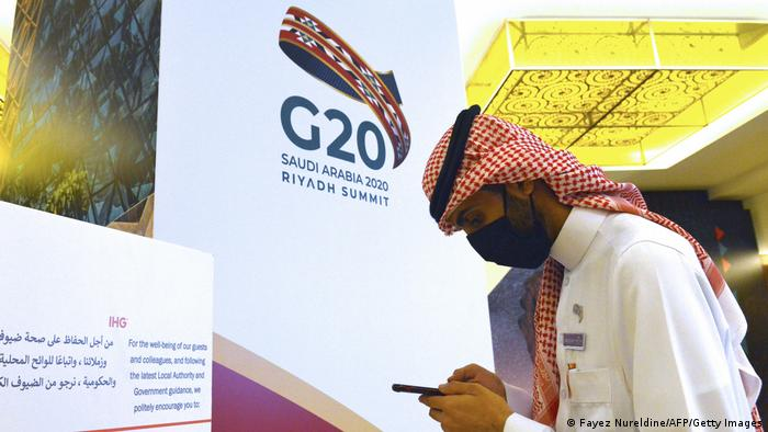 A man stands in front of a G20 sign in Riyadh