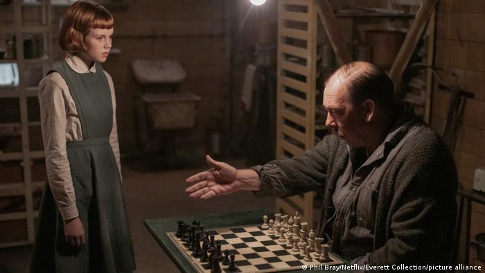 Filmszene aus Das Damengambit. Sie zeigt die Schauspielerin als junges Mädchen (Isla Johnston) in einem Keller, wo ein Mann (Bill Camp) an einem Schachtisch sitzt und ihr einen Platz zuweist.