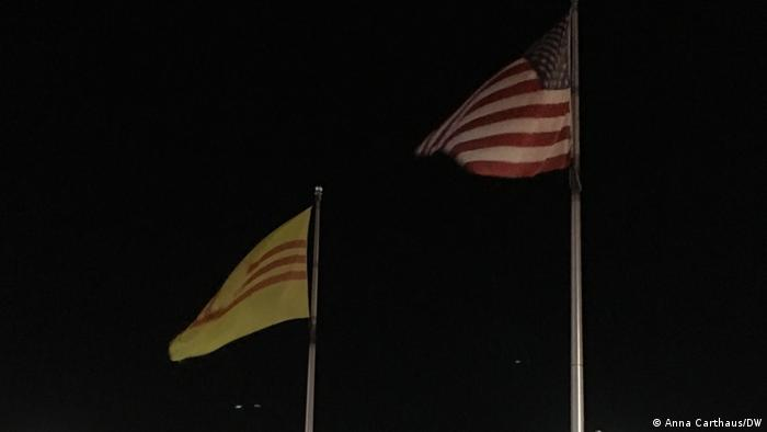 In the middle of the parking lot at the Eden Center in Falls Church, Virginia, hang the flags of the US and South Vietnam, a country that ceased to exist with the fall of Saigon in 1975