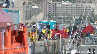 Группа мигрантов у причала в портовом временном лагере