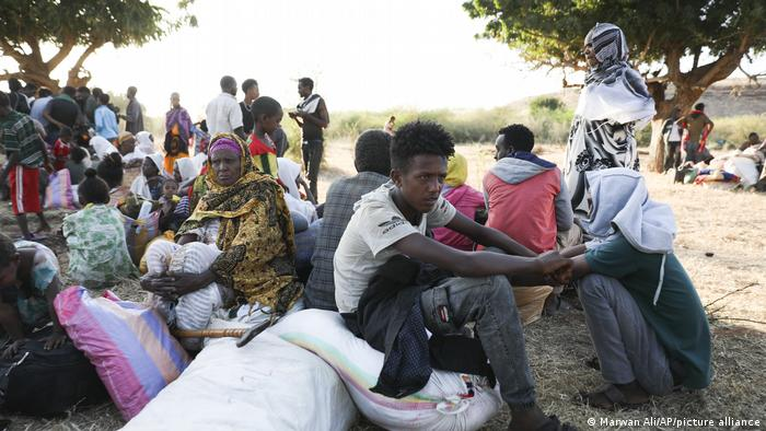 Ethiopian refugees sit in the shade in Sudan