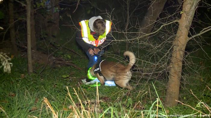 Ein Polizist sucht mit einem Spürhund in einem Waldstück in Berlin nach sterblichen Überresten des vermissten Mannes Foto: Telenewsnetwork/dpa +++ dpa-Bildfunk)
