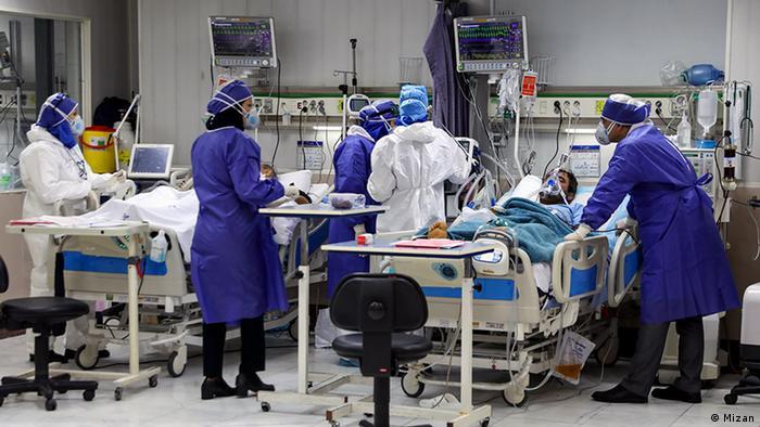 Krankenschwestern und Ärzte in Schutzausrüstung stehen in einem Krankenhauszimmer , in dem in zwei Betten Patienten intensivmedizinisch behandelt werde