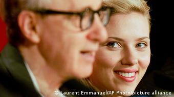 Schauspielern Johansson mit blondem Haar. Sie lächelt Woody Allen an, der im Vordergrund unscharf zu erkennen ist.