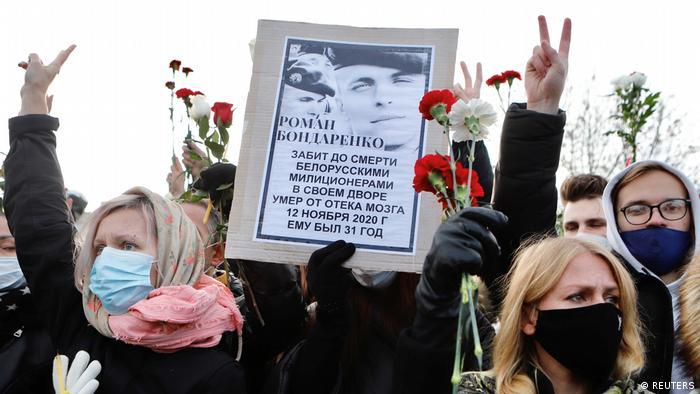 Участники протеста в Беларуси с плакатом в память об избитом до смерти силовиками активисте Романе Бондаренко