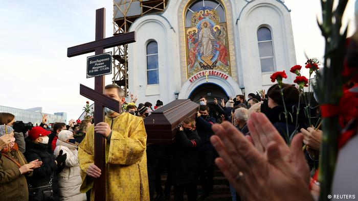 Pole bearers carry the coffin from the Minsk church