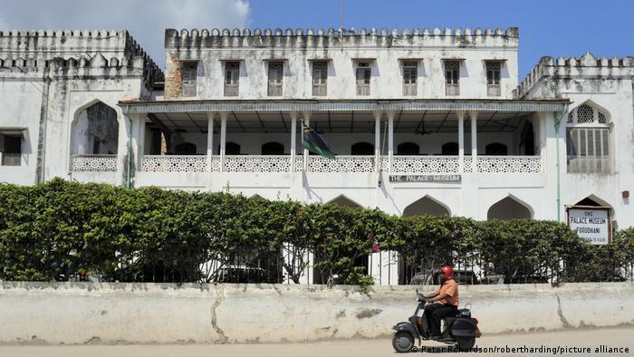 Eine Person auf einem Motorroller fährt an einem Palast vorbei
