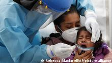 Dr. Victor Hugo Santamaria tests 2-year-old Regina Chavez for COVID-19 as she is held by her mother Edith Monserrat Bautista, in a tent set up to perform rapid coronavirus testing at the TAPO bus station in the Venustiano Carranza borough of Mexico City, Friday, Nov. 20, 2020. Mexico passed the 100,000 mark in confirmed COVID-19 deaths on Thursday, becoming only the fourth country to do so. (AP Photo/Rebecca Blackwell) |