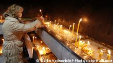 A woman lights candles in the St. Sava church in Belgrade, Serbia, Friday, Nov. 20, 2020. The Serbian Orthodox Church says its head, Patriarch Irinej, has died after testing positive for the coronavirus. He was 90. (AP Photo/Darko Vojinovic) |