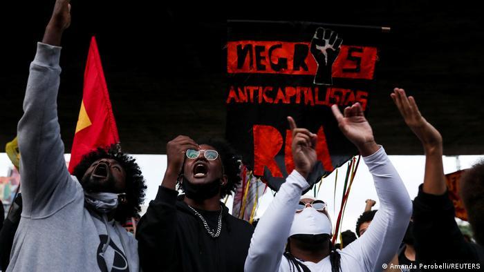 Pessoas negras gritam e gesticulam diante de faixa Negros anticapitalistas