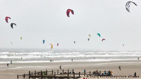 Praia com pipas de kitesurf no céu cinzento