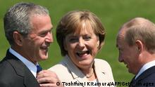 HEILIGENDAMM, GERMANY: US President George W.Bush (L), Russian President Vladimir Putin (R) and German Chancellor Angela Merkel (C) share a joke prior to the family photo session with Outreach countries at G8 summit in Heiligendamm, 08 June 2007 US President George W. Bush spent several hours restricted to his hotel room at the Group of Eight summit on Friday after being struck down by a stomach ailment. AFP PHOTO TOSHIFUMI KITAMURA (Photo credit should read TOSHIFUMI KITAMURA/AFP via Getty Images)
