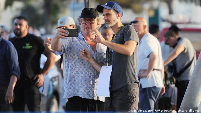 Regisseur Edoardo Ponti schaut mit dem Kameramann in ein Handy (IPA/Fotogramma/picture alliance).
