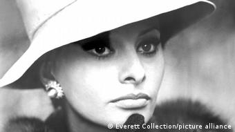 Black and white portrait of Sophia Loren in 1963, wearing a fur-collared coat and a wide-brimmed hat.