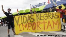 Foto de personas que protestan frente a una sucursal de Carrefour con una pancarta que dice Vidas negras importan tras muerte de Joao Alberto Silveira Freitas