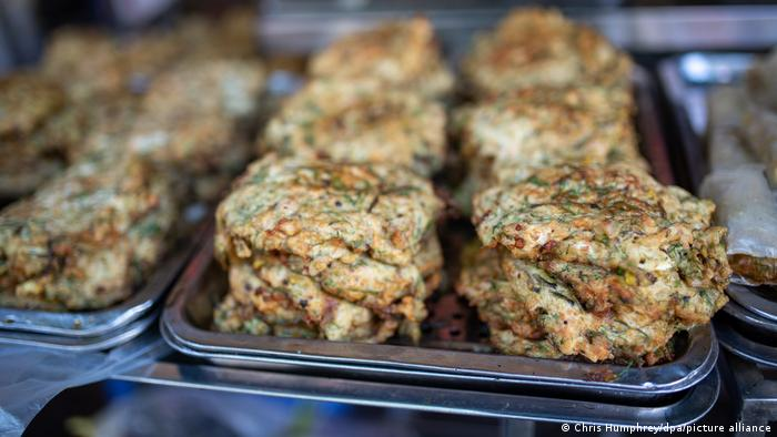 تُقدم وجبة أومليت الدود مع شعيرية الأرز وطبق من صوص السمك الحلو واللاذع