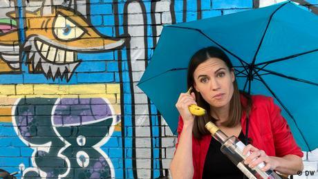 Rachel Stewart von Meet the Germans mit Schirm, Banande und Flasche vor einer Graffiti-Wand