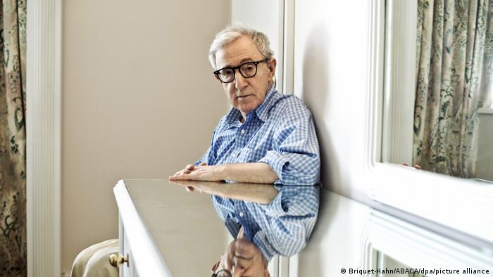 Woody Allen seated by a window, peers at his reflection in the mirror on the surface of a table