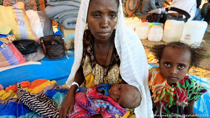 A refugee from Tigray and her two small children at the Um-Rakoba camp in Sudan