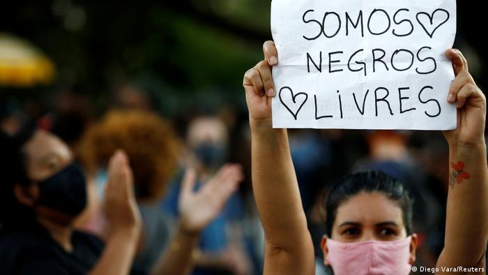 Manifestante de máscara carrega cartaz com os dizeres Somos negros livres