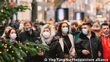 People wearing face masks walk in the city center of Cologne, Germany