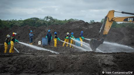 Workers cleaning up oil and fuel along the Napo River after an oil spill in Ecuador