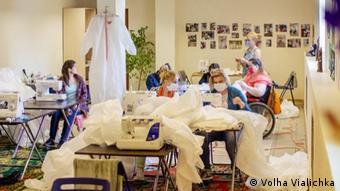 Волонтеры в помещении хосписа шьют защитные костюмы для медиков