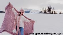 Frau steht mit rosa Decke