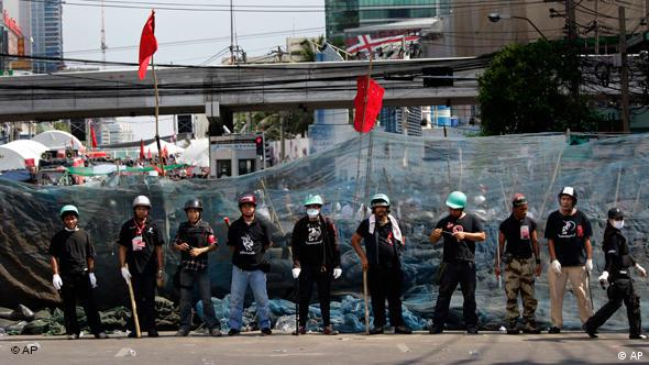 Kette von Regierungsgegnern mit Helmen vor ihrer Barrikade (Foto:ap)