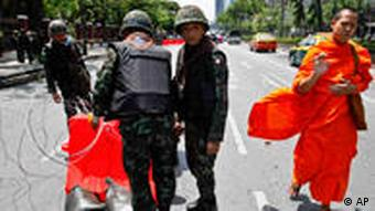 A Thai Buddhist monk moves past Thai soldiers as they erect barricades
