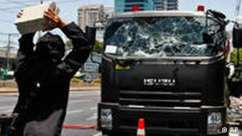 An Anti-government demonstrator throws cement blocks at a truck near Lumpini Park
