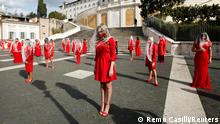 Women dressed in red pose at the Spanish Steps as they record a video to raise awareness of gender-based violence ahead of the International Day for the Elimination of Violence Against Women on November 25, in Rome, Italy, October 26, 2020. REUTERS/Remo Casilli