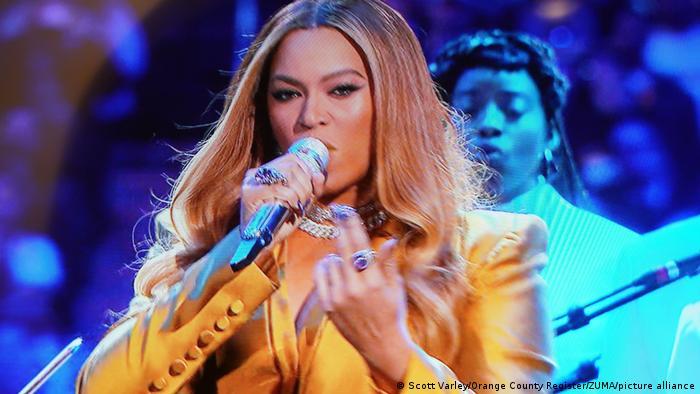 Beyoncé bei einem Auftritt mit Mikrofon in der Hand und goldenem Blazer