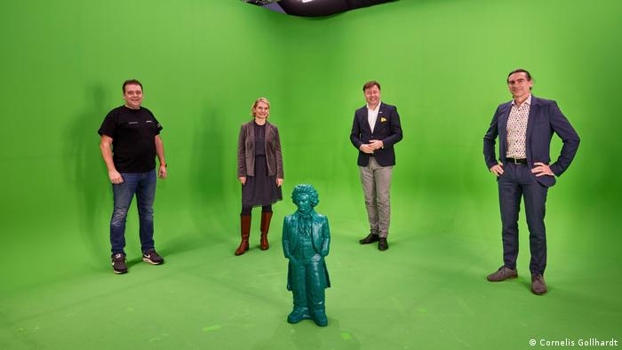 Three men and a woman and a Beethoven statue in a green box