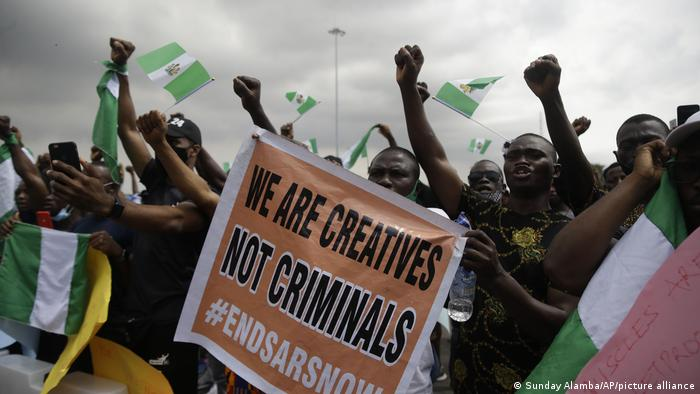 Nigerians displaying banners with the hashtag #EndSARS to protest against police brutality