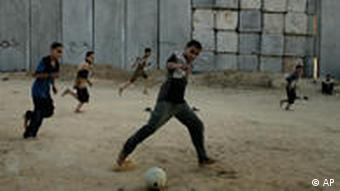 Palestinian boys play soccer next to the concrete blocks that separate the southern Gaza Strip