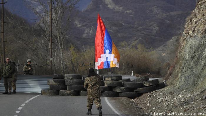 Ein armenischer Soldat mit Berg-Karabach-Flagge an einem Kontrollpunkt an der neuen Grenze zum Bezirk Kelbadschar