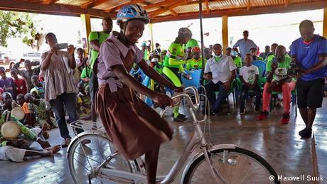 Ghana Schulkind Rebecca sitzt mit Helm auf ihrem neuen Fahrrad, im Hintergrund Mitglieder des Fahrradclubs