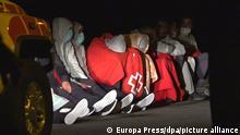 24.11.2020, Spanien, Lanzarote: Migranten sitzen umhüllt in Decken des Roten Kreuzes auf dem Boden. Beim Untergang ihres Holzbootes aus Nordafrika sind an der Küste der zu Spanien gehörenden Kanareninsel Lanzarote mindestens sieben Menschen ertrunken. Foto: Europa Press/EUROPA PRESS/dpa +++ dpa-Bildfunk +++ |