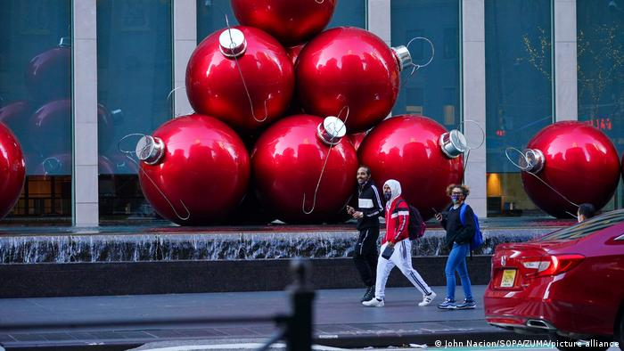 People walk past huge red x-mas ball ornaments