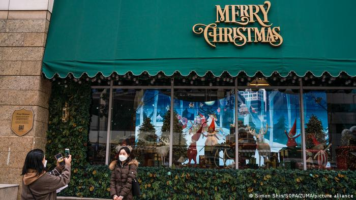 A woman takes a photo of another woman standing in front of a shop window decorated for Christmas
