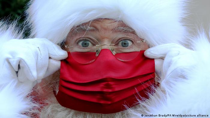 Face of a man dressed as Santa Claus, wearing a red mask