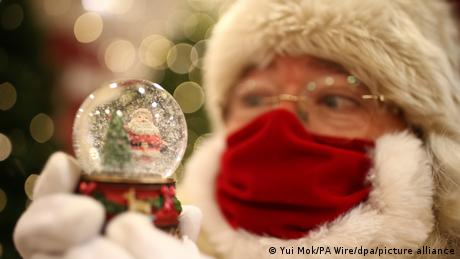 A man dressed as Santa Claus wears a red mask and holds a snow globe