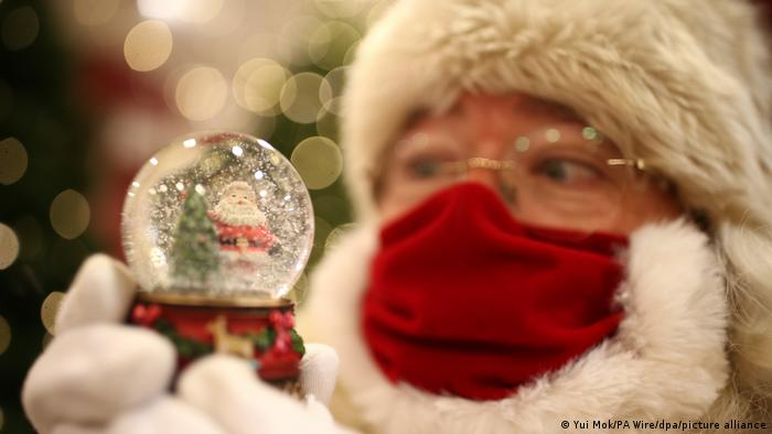 A person dressed as Santa looking into a snow globe