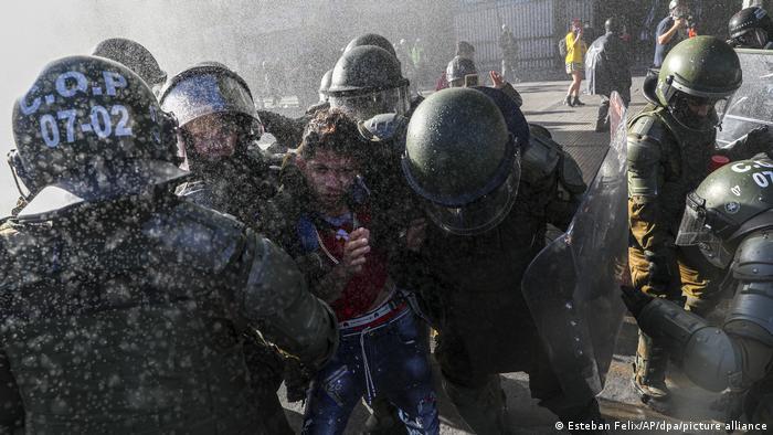 Foto de manifestante detenido por policías de Chile
